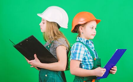 school project. small girls repairing together in workshop. Labor day. 1 may. Little kids in helmet with tablet. Foreman inspector. Repair. school project concept. children work for school project