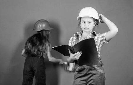 small girls repairing together in workshop. Labor day. 1 may. engineering idea. Future career. Little kids in helmet with tablet and roller. Foreman inspector. Repair. choosing a career. best career