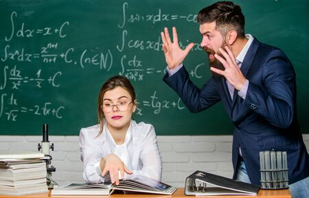 Man unhappy communicating. School principal talking about punishment. Conflict situation. School conflict. Demanding lecturer. Teacher strict serious bearded man having conflict with student girl Stock Photo