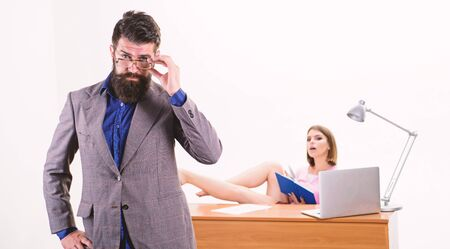 An intellectual look of hipster. Hipster fixing his glasses while woman working in background. Bearded hipster and pretty coworker in office. Hipster with long beard in business casual style