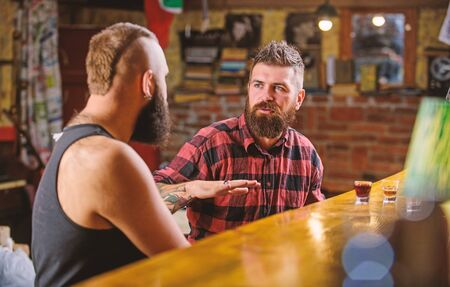 Friday relaxation in bar. Friends relaxing in bar or pub. Soulmates drunk conversation. Hipster brutal bearded man spend leisure with friend at bar counter. Men relaxing at bar. Strong alcohol drinks Stockfoto