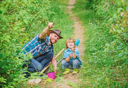 Joyful weekend. father and son in cowboy hat on ranch. Eco farm. small boy child help father in farming. hoen, pot and shovel. Garden equipment. happy earth day. Family tree nursering Archivio Fotografico