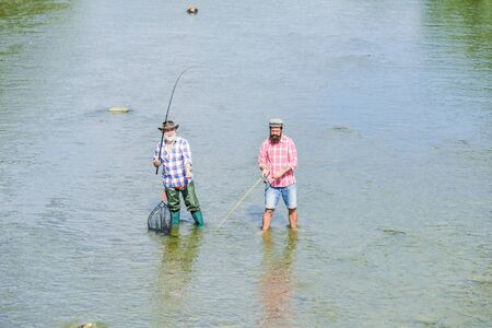 Teach man to fish and you feed him for lifetime. Summer weekend. Happy fisherman with fishing rod and net. Hobby and sport activity. Male friendship. Father and son fishing. Fishing together