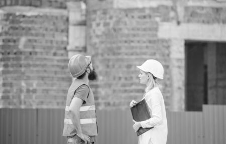 Discuss progress project. Construction industry concept. Woman engineer and bearded brutal builder discuss construction progress. Construction project management. Building industrial project