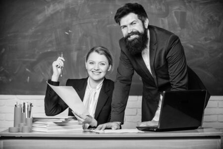 Studying together is fun. teacher and student on exam. businessman and happy secretary. business couple use laptop and documents. paper work. office life. back to school. Non-formal education