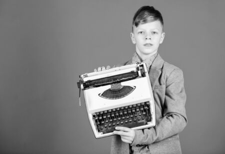 Retrospective study. Boy hold retro typewriter on blue background. What to do with this thing. Out of date. I need modern gadget instead this retro. Outdated gadget. Retro and vintage. Yard sale Stock Photo