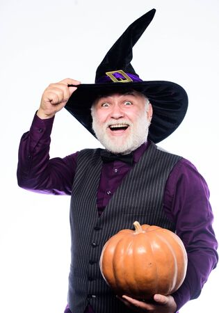halloween traditions. evil wizard hold orange pumpkin. bearded man ready for halloween party. Stargazer in holiday costume. Traditional food. happy halloween. mature man magician in witch hat 写真素材