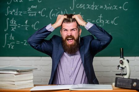 Difficult work. Emotional burnout. Teacher give up. Hate his job. Man desperate teacher in classroom. Going mad. Teaching dumb students. No hope for better. Tired and exhausted. Teacher mature man Stock Photo