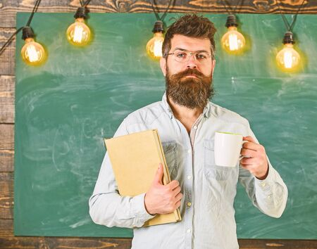 Teacher in eyeglasses holds book and mug of coffee or tea. School break concept. Man with beard on calm face in classroom. Scientist holds book and mug of coffee, chalkboard on background, copy spac