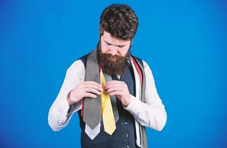 Discover trendy mens fashion in our shop. Bearded man choosing luxury necktie in menswear shop. Shop assistant offering wide choice of finest neckties. Shop for mens clothes and accessories