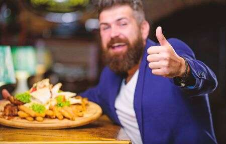Relax after hard day. Delicious food. Businessman formal suit sit at restaurant. Man received meal with fried potato fish sticks meat. He deserve delicious meal. Enjoy your meal. High calorie snack