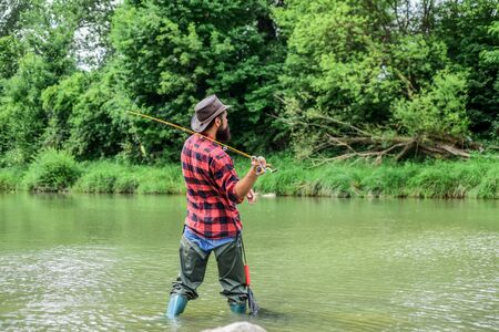 Fisherman catching fish. Teach man to fish. Fishing outdoor sport. Fishing hobby. Calm and tranquil. Patience and waiting. Fly fishing may well be considered most beautiful of all rural sports