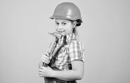 Tools to improve yourself. Repair. Future profession. Builder engineer architect. Kid worker in hard hat. Child care development. small girl repairing with hammer in workshop. she loves her job Foto de archivo