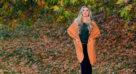 Cozy outfit ideas for weekend. Woman walk sunset light. Comfortable outfit. Girl adorable blonde posing in warm and cozy outfit autumn nature background defocused. Cozy casual outfits for late fall Archivio Fotografico