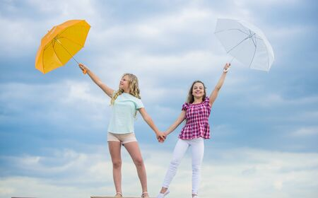 Going crazy together. positive and bright mood. best friends. school time. autumn season. rainy weather forecast. fall fashion. Feeling protected at this autumn day. happy small girls with umbrella Archivio Fotografico - 129457890