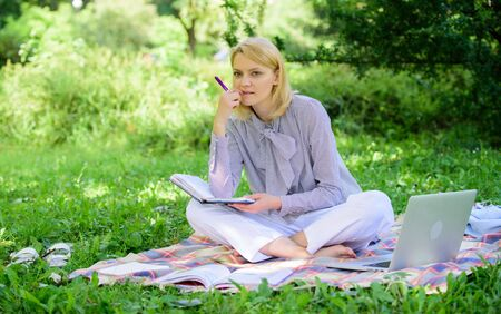 Freelance career concept. Guide starting freelance career. Become successful freelancer. Woman with laptop sit on rug grass meadow. Girl with notepad write note. Business lady freelance work outdoors