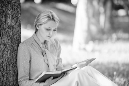 Girl concentrated sit park lean tree trunk read book. Reading inspiring books. Bestseller top list. Books every girl should read. Relax leisure an hobby concept. Best self help books for women Foto de archivo