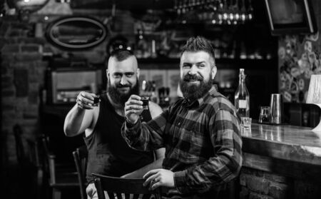 Men relaxing at bar. Friendship and leisure. Friday relaxation in bar. Friends relaxing in pub. Hipster brutal bearded man spend leisure with friend at bar counter. Order drinks at bar counter