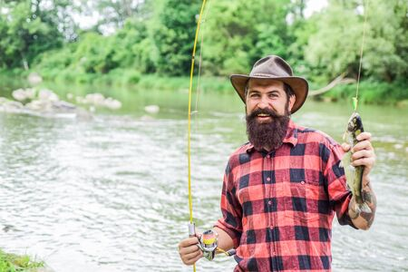 Fisher fishing equipment. Rest and recreation. Fish on hook. Brutal man stand in river water. Man bearded fisher. Fisher masculine hobby. Fishing requires to be mindful and fully present in moment