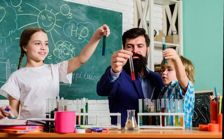Chemistry themed club. Discover and explore properties of substances together. Kids can grow in area of club such as science. School club education. Teacher and pupils test tubes in classroom