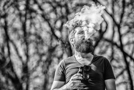 White clouds of flavored smoke. Smoking electronic cigarette. Man long beard relaxed with smoking habit. Man with beard and mustache breathe out smoke. Stress relief concept. Bearded man smoking vape Stockfoto