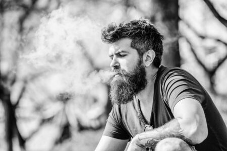 Health safety and addiction. inhaling vapor. man smoking e-cigarette. hipster man hold vaping device. Mature hipster with beard. Bearded brutal male smoking electronic cigarette. Bearded and stylish