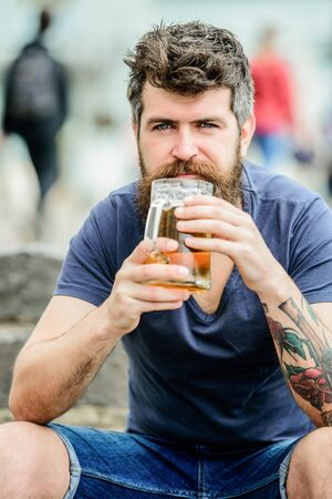 Guy having rest with cold draught beer. Hipster relaxed drinking beer outdoor. Light ales or dark stouts drink them all. Man with beard and mustache hold beer glass outdoors. Cafe summer terrace