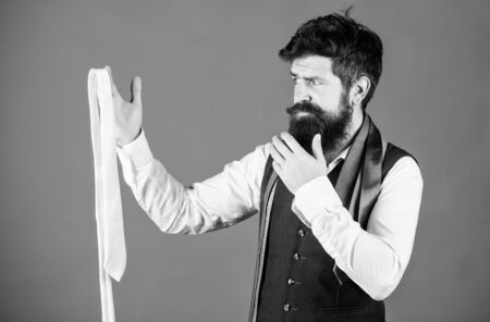 How to select tie. When dressing in suit necktie often add dash of flavor to overall outfit. Man bearded hipster hold few neckties. Guy with beard choosing necktie. Perfect white silk necktie