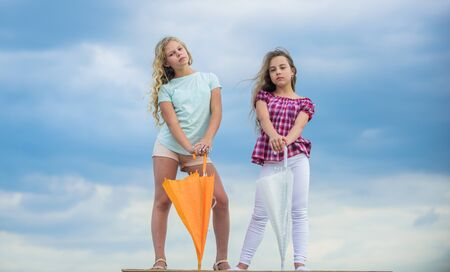 Ready for any weather. Girls friends with umbrellas cloudy sky background. Windy or rainy we are prepared. Freedom and freshness. Weather forecast. Weather changing. Carefree children outdoors