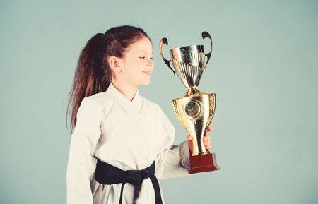 Niño fuerte y seguro. Niña pequeña en kimono blanco con cinturón. Niño luchador de Karate. Concepto de deporte de Karate. Habilidades de autodefensa. El karate da sensación de confianza. Celebre el logro Foto de archivo