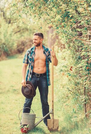 Commitment and responsibilities. Agriculture concept. Planting in garden. Tree planting tradition. Growing plants. Man handsome muscular torso with watering can and shovel. Arbor day. Planting trees Stock Photo