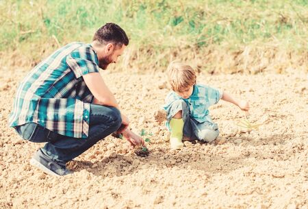 small boy child help father in farming. new life. soils and fertilizers. happy earth day. Supporter of environment. father and son planting flowers in ground. rich natural soil. Eco farm. earth day Stockfoto