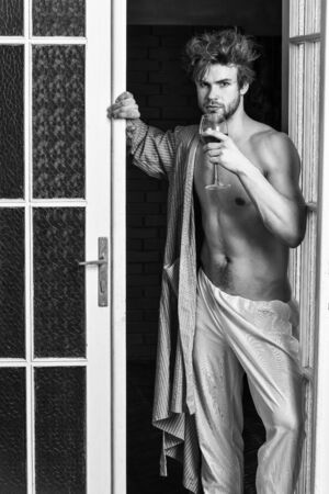 Sexy lover concept. Bachelor sexy body chest and belly. Guy shimmering sweaty skin wear bathrobe. Sexy attractive macho tousled hair coming out through bedroom door. Man with sexy torso drink wine