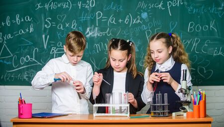 School laboratory. Group school pupils study chemical liquids. Test tubes with colorful substances. Girls and boy student conduct school experiment with liquids. Check result. School chemistry lesson Stock Photo