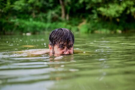 Deep dangerous water. Relaxation and rest. Swimming sport. Swimming skills. Refreshing feeling. Man enjoy swimming in river or lake. Submerge into water. Freshness of wild nature. Summer vacation Zdjęcie Seryjne