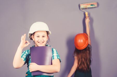 Little kids in helmet with tablet and roller. engineering idea. Future career. Painting wall. Foreman inspector. Labor day. 1 may. small girls repairing together in workshop. Trust me I am an expert