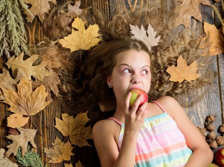 Munch, crunch. Vitamin food for healthy growth. Cute girl child with ripe autumn crops. Little girl biting apple. Small girl likes the taste of apple fruits. Organic and natural food for kids health 写真素材