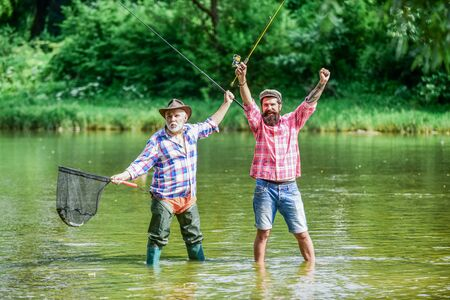 Bearded men catching fish. Master baiter. Mature man with friend fishing. Summer vacation. Happy cheerful people. Fisherman with fishing rod. Activity and hobby. Fishing freshwater lake pond river 写真素材
