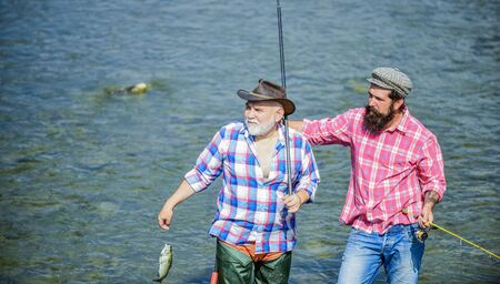 Happy fisherman with fishing rod and net. Hobby and sport activity. Male friendship. Men stand in water. Nice catch concept. Fishing team. Father and son fishing. Summer weekend. Fishing together 写真素材