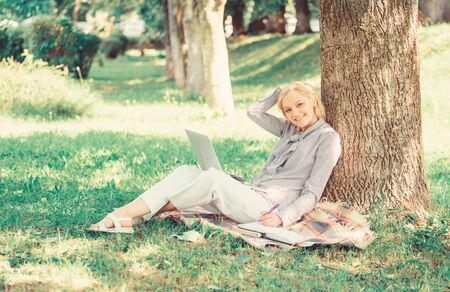 Woman with laptop computer work outdoors lean on tree trunk. Education technology and internet concept. Girl work with laptop in park sit on grass. Natural environment office. Work outdoors benefits