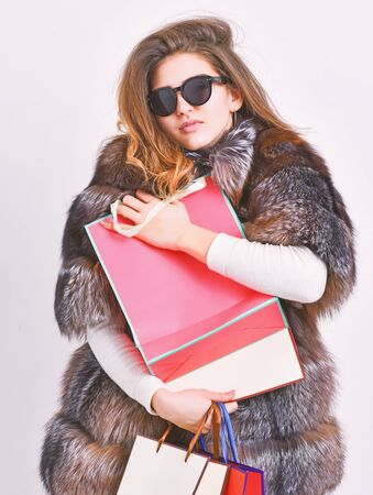 Discount and sale. Buy with discount on black friday. Shopping with promo code. Woman shopping luxury boutique. Girl wear sunglasses and fur coat shopping white background. Lady hold shopping bags Stock Photo