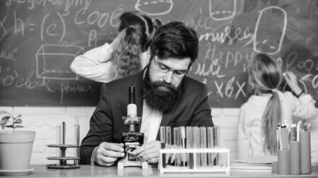 Man bearded teacher work with microscope and test tubes in biology classroom. Explaining biology to children. Biology plays role in understanding of complex forms of life. School teacher of biology