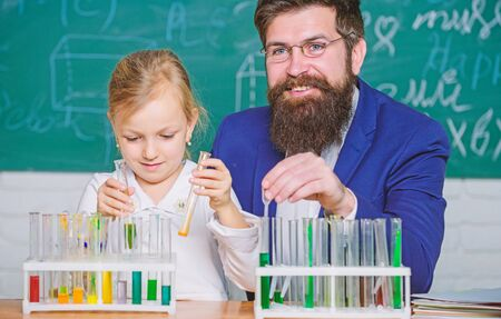 Explaining chemistry to kid. How to interest children study. Fascinating chemistry lesson. Man bearded teacher and pupil with test tubes in classroom. Private lesson. School chemistry experiment