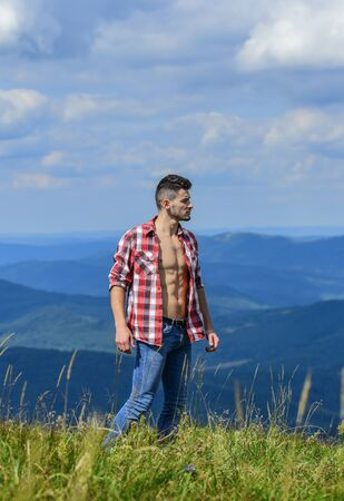 Hiking concept. Power of nature. Man unbuttoned shirt stand top mountain landscape background. Muscular tourist walk mountain hill. Strong hiker muscular torso. Athlete muscular guy relax mountains