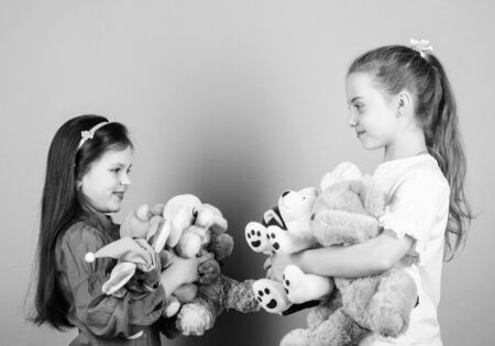 Relaxing together. playground in kindergarten. little sisters girls playing game in playroom. small girls with soft bear toys. happy childhood. handmade. sewing and diy crafts. toy shop. children day Stok Fotoğraf