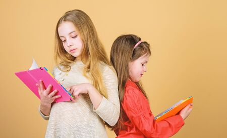 Friendship and sisterhood. students reading a book. School project. workbooks for writing. Back to school. small girls with note books. happy little children ready for lesson. Inspired to work hard Stock fotó