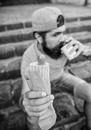 Man bearded bite tasty sausage and drink paper cup. Street food so good. Urban lifestyle nutrition. Carefree hipster eat junk food while sit on stairs. Hungry man snack. Junk food. Guy eating hot dog