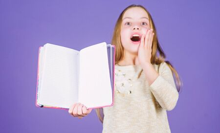 She is excellent in reading. Happy little girl enjoy reading books. Cute small child happy smiling with open book for home reading. Education in reading, copy space