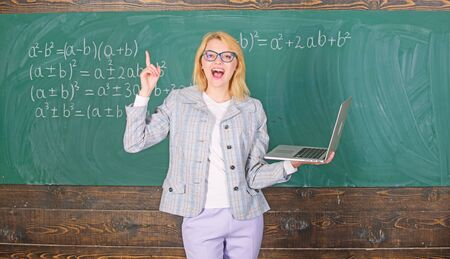 Online schooling concept. Woman wear eyeglasses holds laptop surfing internet. Educator smart clever lady with modern laptop searching information chalkboard background. Educational site for teachers Stockfoto