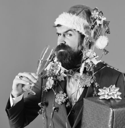 Man in smart suit, Santa hat and garlands on blue